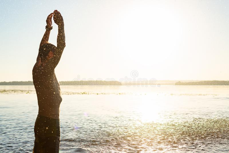 Joyful guy raises her hands with splashes of water. In the rays of the rising sun - beach holidays. Back view, backlight royalty free stock photos