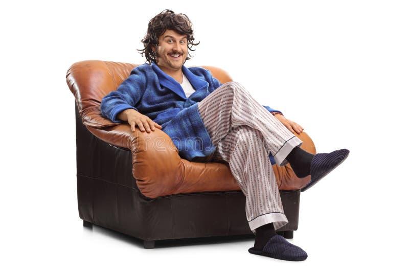 Joyful guy sitting on a brown armchair. Joyful guy with retro hairstyle sitting on a brown leather armchair isolated on white background stock photo