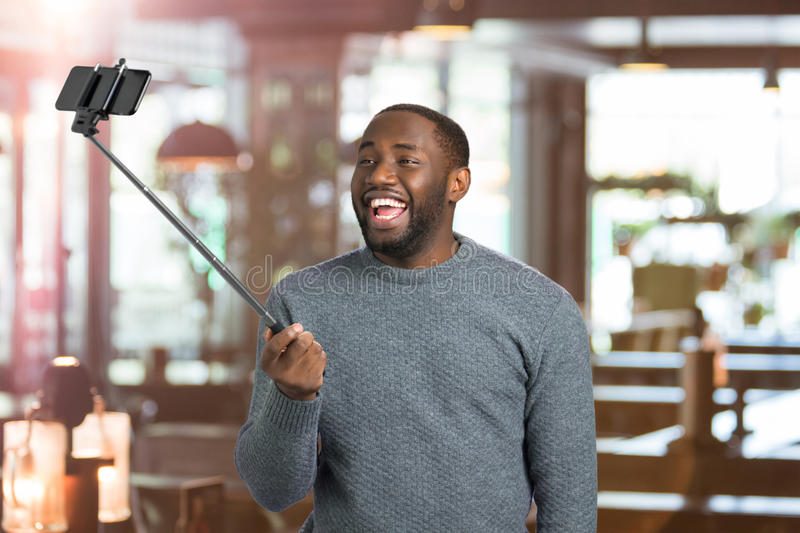 Joyful guy taking picture with selfie stick. Happy young man taking selfie holding monopod on blurred background. Taking sweet moments with selfie stick stock photos
