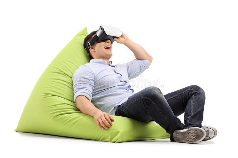 Joyful guy using virtual reality headset and lying on beanbag. Joyful guy using a virtual reality headset and lying on a beanbag isolated on white background royalty free stock photos