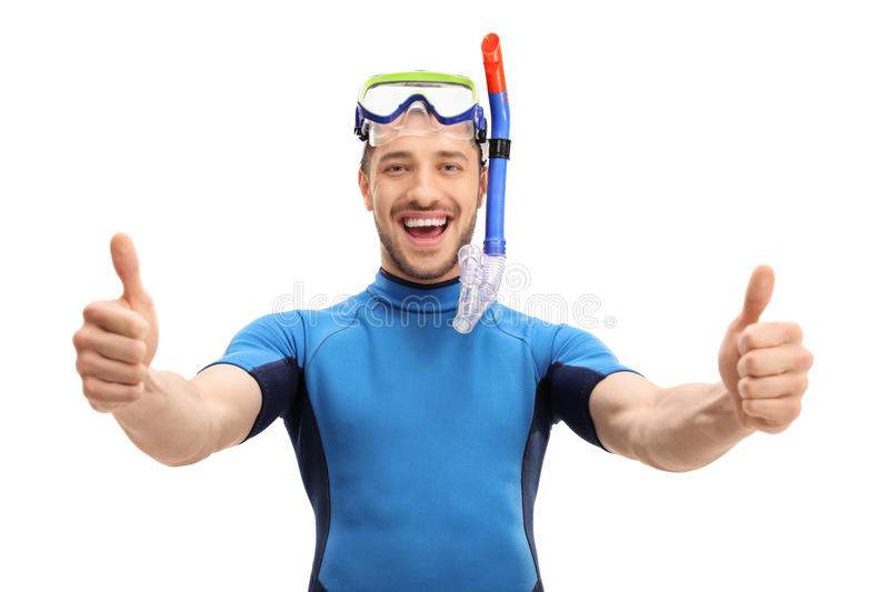 Joyful guy in a wetsuit making a thumbs up gesture. Joyful guy in a wetsuit with a diving mask and a snorkel making a thumbs up gesture isolated on white royalty free stock image