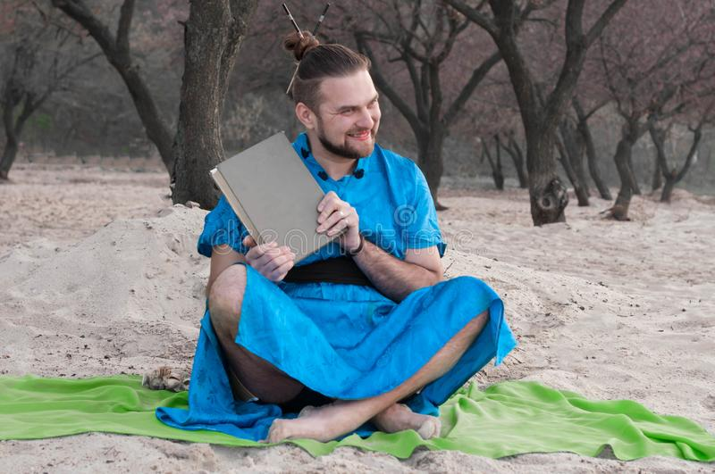 Joyful handsome bearded man in blue kimono sitting, swinging with book, laughing and looking away royalty free stock photography