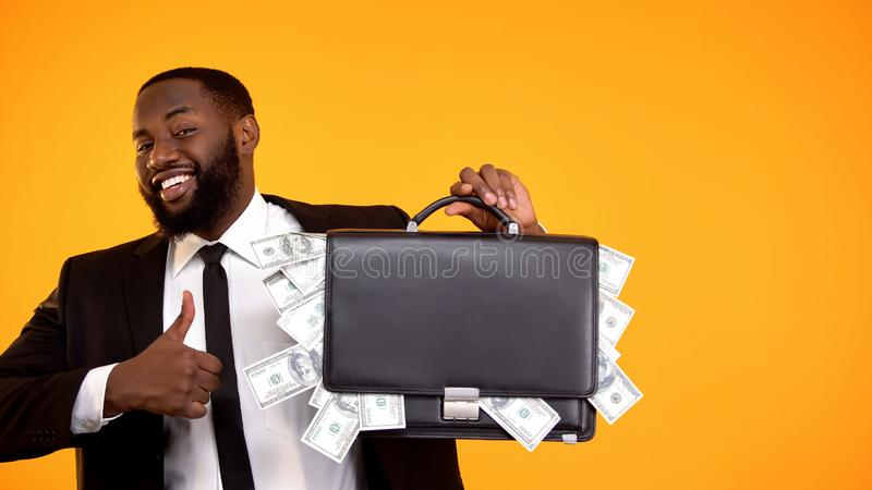 Joyful handsome black man in suit holding handbag with cash, showing thumbs-up royalty free stock photography