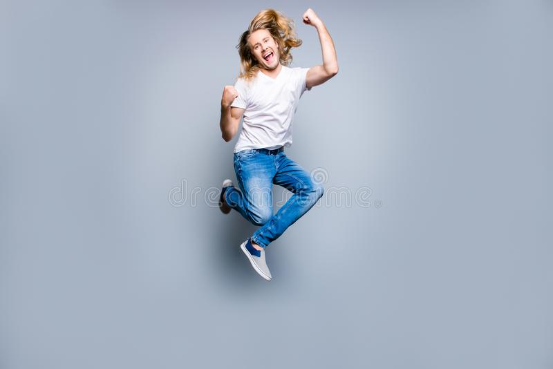 Joyful happy excited young man with blonde long hair is screaming and jumping up with raised fists, isolated on grey background stock photography