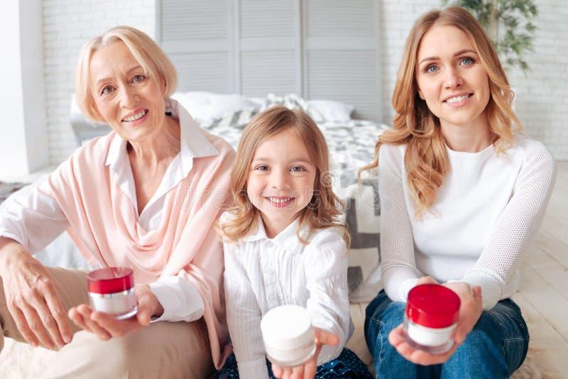 Joyful happy family showing you bottles of cream royalty free stock image