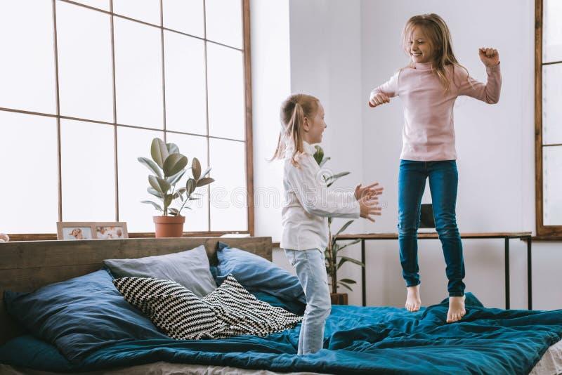 Joyful happy girls jumping on the bed royalty free stock photo