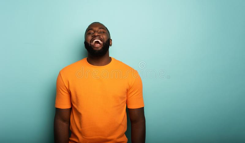 Joyful and happy guy over cyan background. Joyful and happy black guy over cyan background stock images