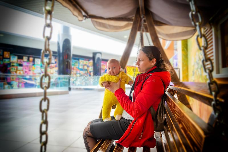 Joyful and happy mom with a child on a bench in a shopping center royalty free stock photo