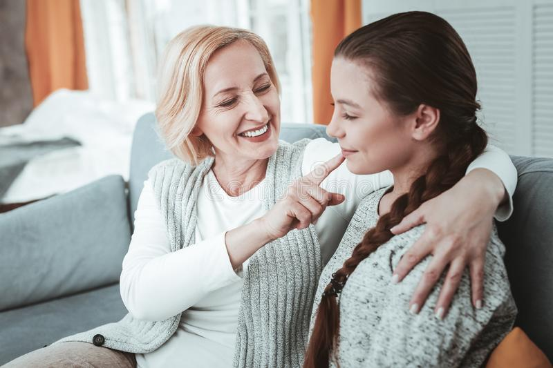 Joyful happy woman touching her granddaughters nose stock image