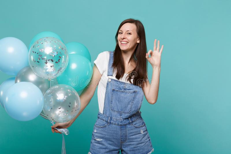 Joyful happy young woman in denim clothes showing OK gesture, celebrating and holding colorful air balloons isolated on. Blue turquoise wall background royalty free stock image