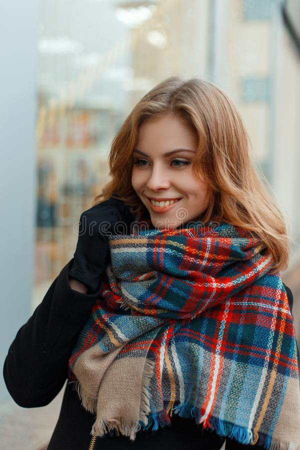 Joyful happy young woman in a fashionable warm wool scarf in a stylish black coat in black gloves is standing and smiling royalty free stock images