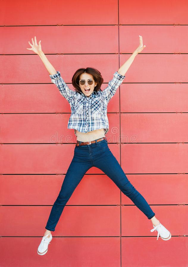 Joyful happy young woman jumping against red wall. Excited beautiful girl portrait stock photography