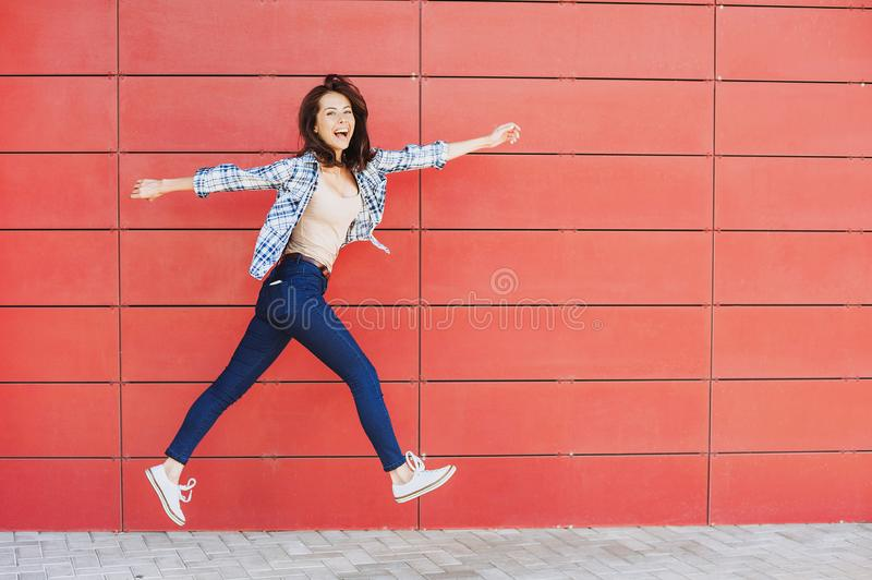 Joyful happy young woman jumping against red wall. Excited beautiful girl portrait royalty free stock image