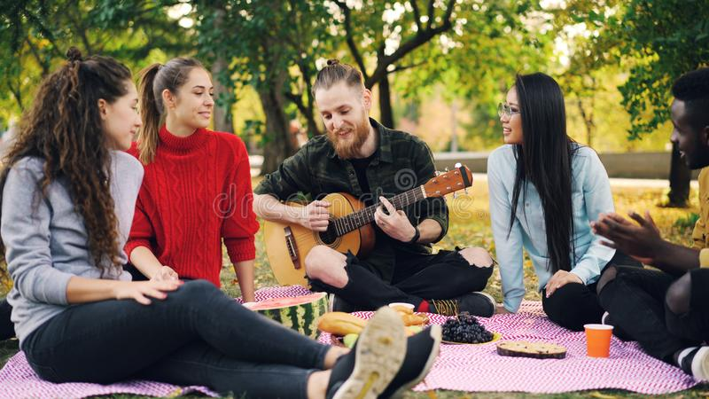 Joyful hipster is singing and playing the guitar sitting on blanket in park with friends and having fun, people are royalty free stock image