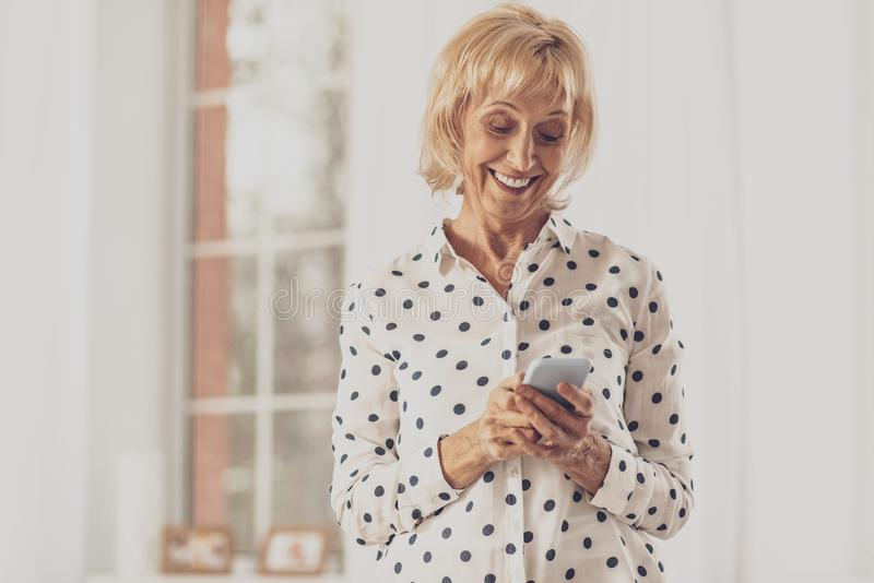 Joyful housewife typing friendly message. Online communication. Attractive blonde woman expressing positivity while looking at her gadget royalty free stock photo