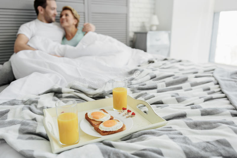 Download Joyful Husband And Wife Enjoying Breakfast In Bedroom Stock Photo