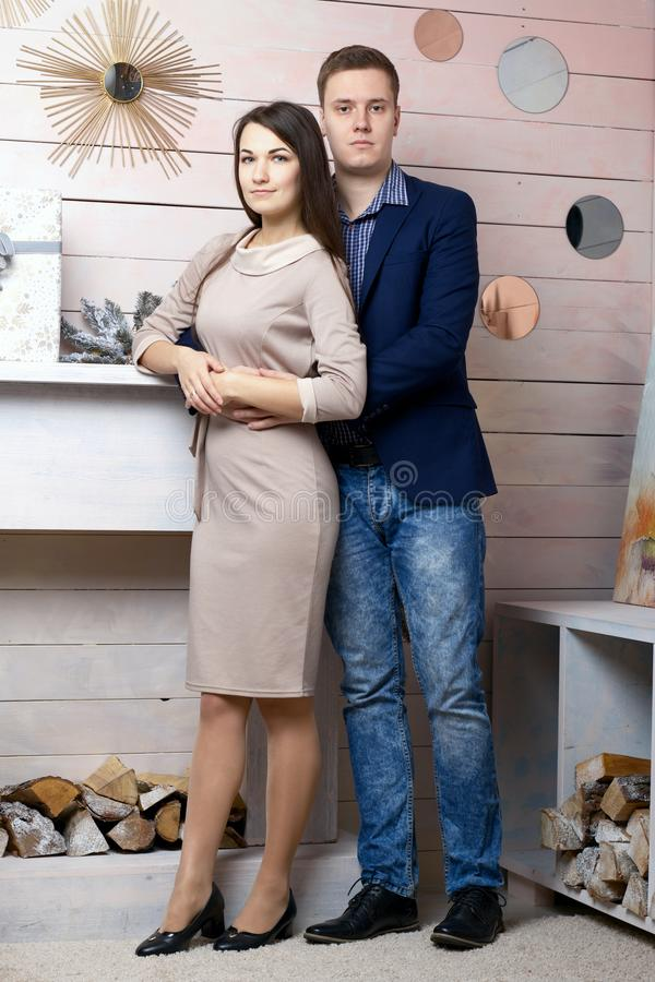 Joyful husband and wife posing by the decorative fireplace. Festive clothes and decorations royalty free stock photo