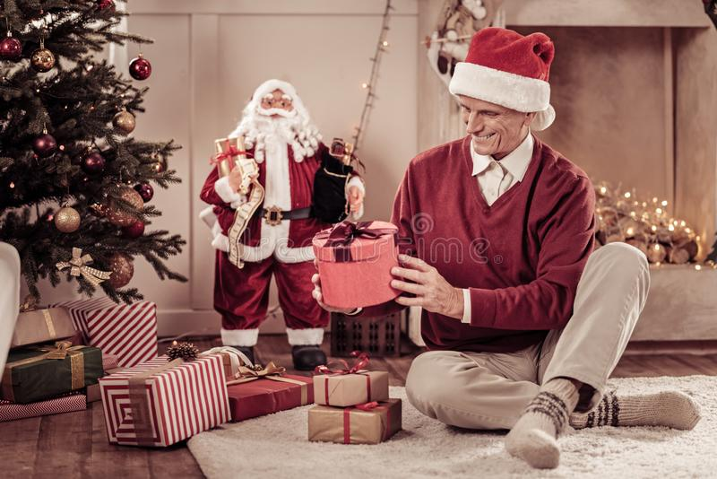 Joyful interested man sitting and holding a gift. Its for me. Joyful interested senior man in a red hat sitting on the floor near the Christmas-tree smiling and royalty free stock image