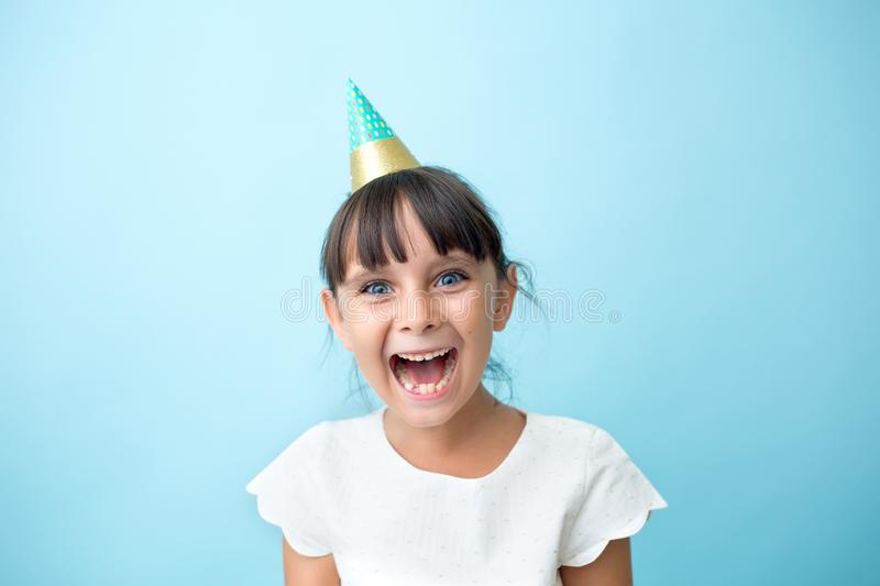 Joyful kid with a cone hat. Party girl with a big smile stock image