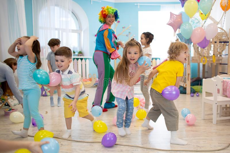 Joyful kids and clown play with color balloon on birthday party stock photography