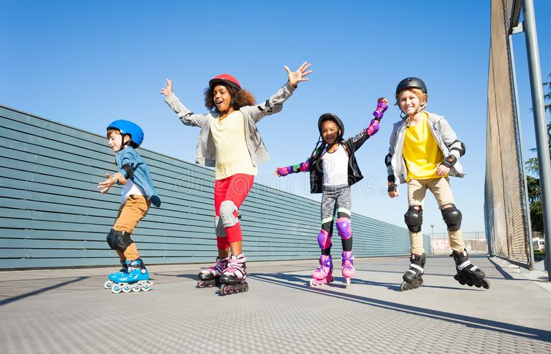Joyful kids rollerblading outdoors at sunny day. Four preteen kids, joyful in-line skaters in helmets and protective gear, playing together outdoors in summer royalty free stock image
