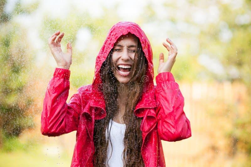 Joyful kvinna som leker i regn arkivbild