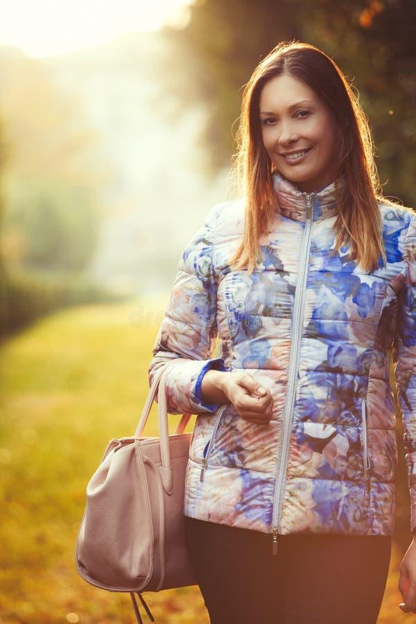Joyful kvinna utomhus Serenitet och fred Kvinnlig handväska royaltyfri foto