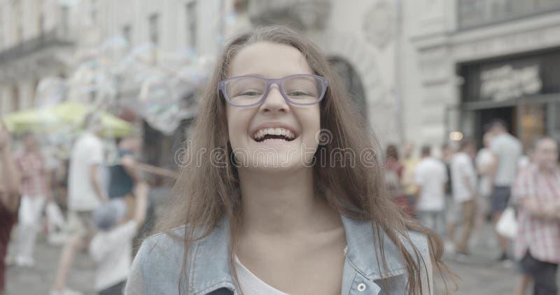 Joyful laughing girl. Lovely little kid in purple eyeglasses is smiling at camera. Emotional Portrait. Huge crowd of stock images
