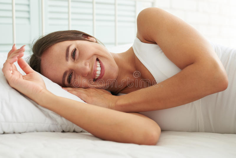 Joyful and laughing softly woman sleeping in bed her head resting on a pillow and hands beside her face royalty free stock image