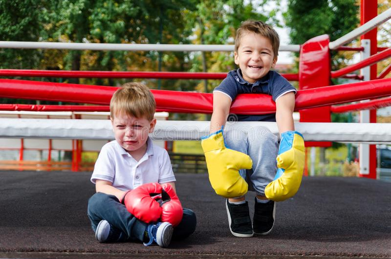 The joyful laughter of the winner and the bitter tears of the lo. Two boys three years in a boxing ring. Taste of victory. The joyful laughter of the winner and royalty free stock photo