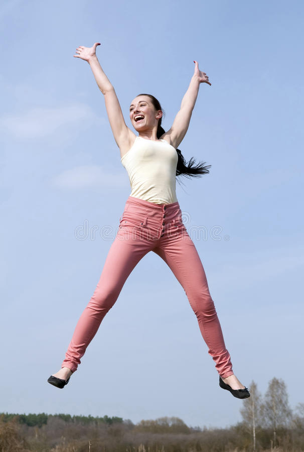 Joyful leap of young woman stock images