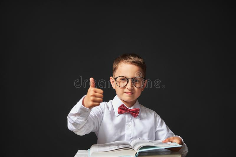 Joyful little boy with glasses and a book in his hands sitting at the table. a happy child learns to read a book. reading stock photography