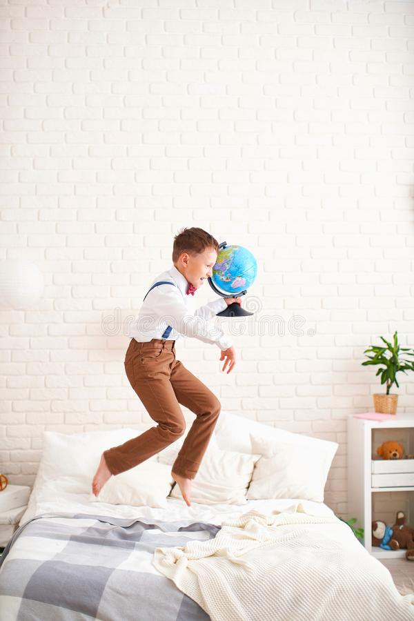 Joyful little boy jumps on the bed with a globe in his hands and enjoys the beginning of the school year. happy child is about to stock images