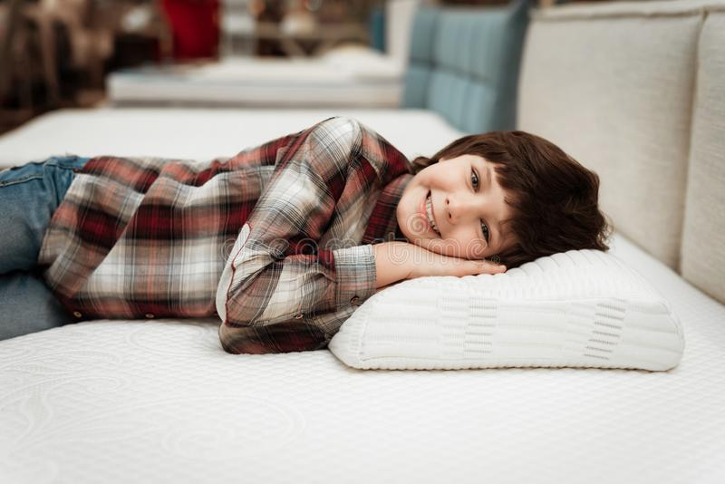 Joyful little boy lies on orthopedic pillow in mattress store. Check for softness of orthopedic furniture. Joyful little boy lies on orthopedic pillow in stock photo