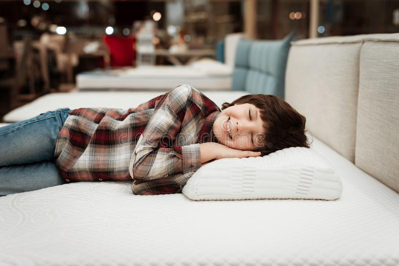 Joyful little boy lies on orthopedic pillow in mattress store. Check for softness of orthopedic furniture. Joyful little boy lies on orthopedic pillow in royalty free stock photo