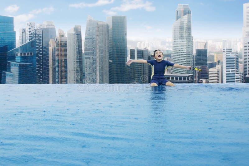 Joyful little boy sitting on the poolside stock photo