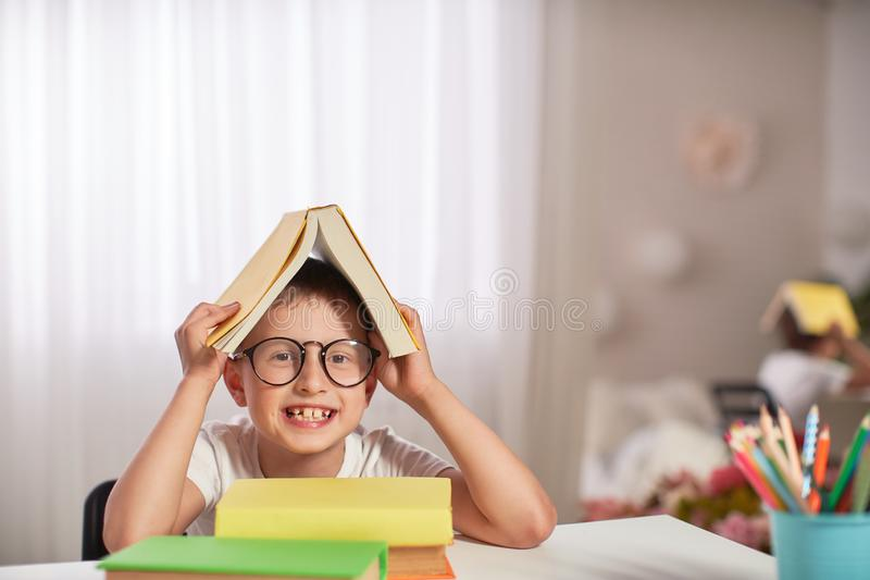 Joyful little boy sitting at the table with pencils and textbooks. Happy child pupil doing homework at the table stock photo