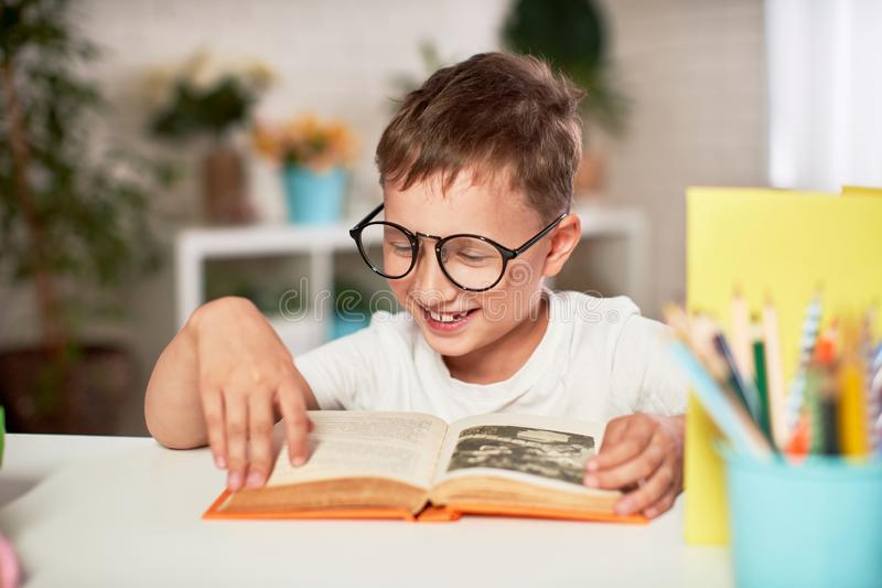 Joyful little boy sitting at the table with pencils and textbooks. Happy child pupil doing homework at the table stock photos