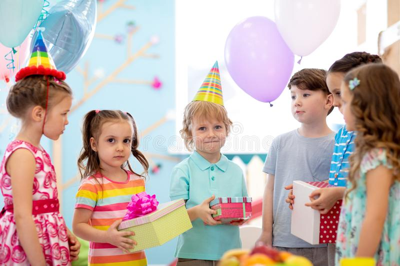 Joyful little kid boy receiving gifts at birthday party. Holidays, birthday concept. stock photography