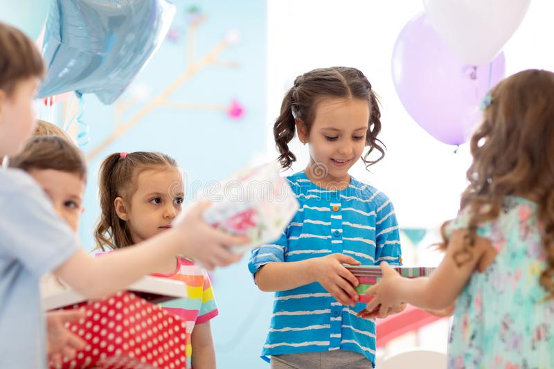 Joyful little kid girl receiving gifts at birthday party. Holidays, birthday concept. royalty free stock photography