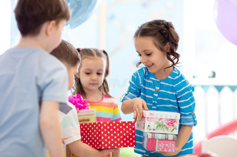 Joyful little kid girl receiving gifts at birthday party. Holidays, birthday concept. stock photos