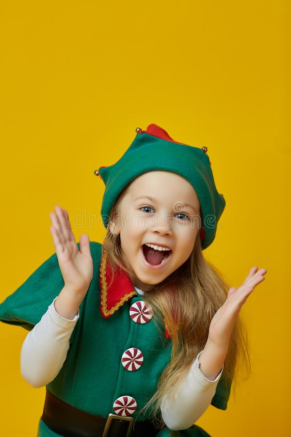 Joyful little girl in a carnival costume with beautiful blond hair over a yellow background. Children`s style stock photo