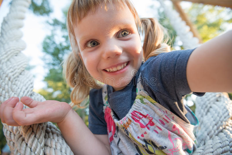 Joyful little girl with funny face, taking selfie royalty free stock images