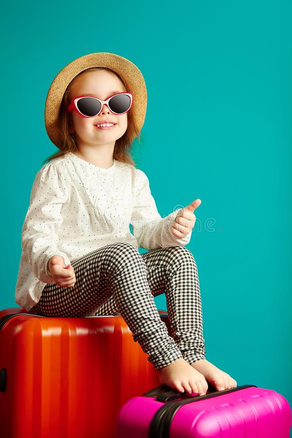 Joyful little girl is going to trip, sitting on suitcases, wearing a straw hat and sunglasses, shows thumbs up, portrait stock photo