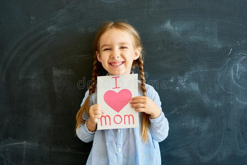 Joyful Little Girl Holding Greeting Card for Mom royalty free stock photos