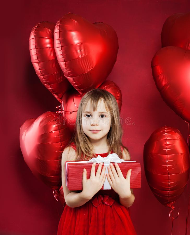 Joyful little girl in red tulle dress holding birthday gift box on red balloons background. Cute child smiling royalty free stock images