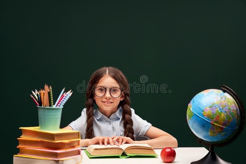 Joyful little girl sitting at the table with pencils and books textbooks. Happy child pupil doing homework at the table royalty free stock photography