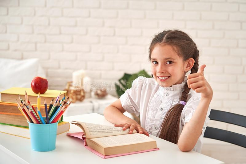 Joyful little girl sitting at the table with pencils and textbooks. Happy child pupil doing homework at the table.beautiful stock photos