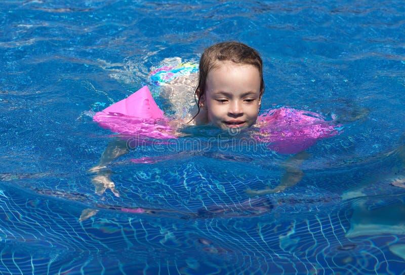 Joyful little girl swimming in the pool. stock images