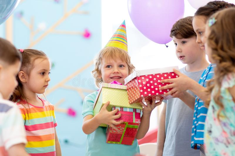 Joyful little kid boy receiving gifts at birthday party. Holidays, birthday concept. royalty free stock images